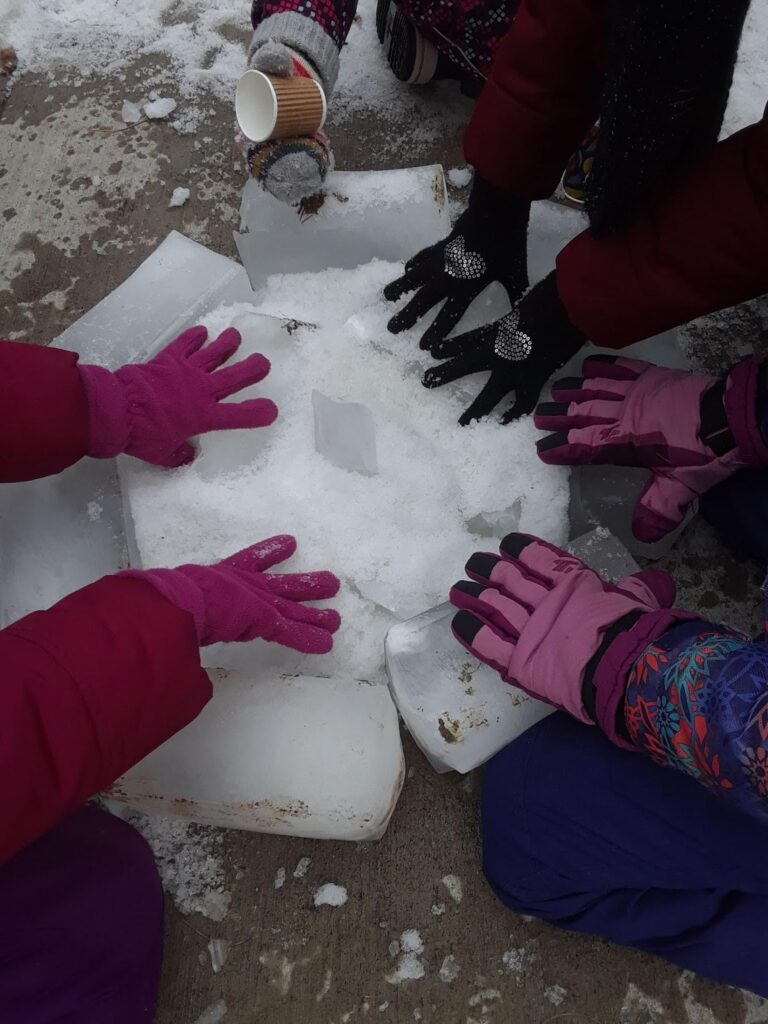 Colourful gloved hands surround a bonfire made up of ice blocks and snow
