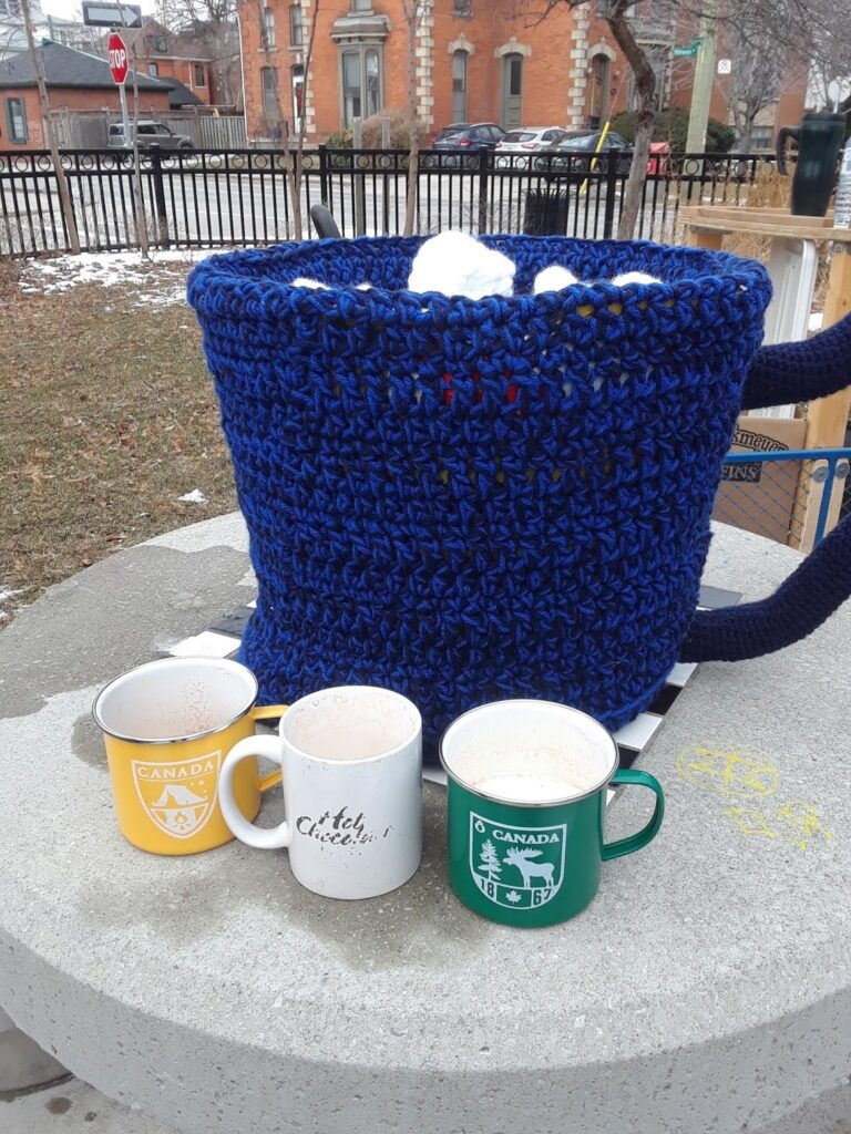 A large crocheted mug sits on a checkerboard park table with three regular-sized mugs in front of it